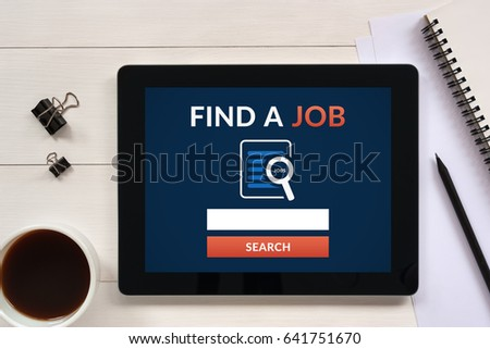 Find a job concept on tablet screen with office objects on white wooden table. All screen content is designed by me. Flat lay