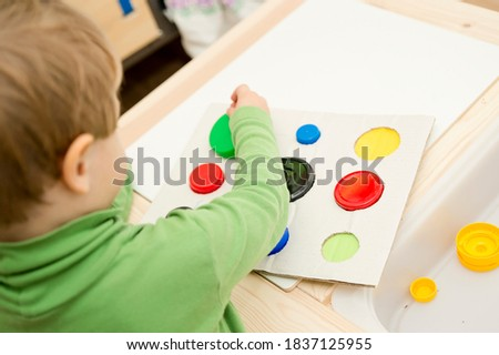 Photo of  find a match. child inserting different size and color plastic caps in matching holes.ergo therapy task for education and brain exercise. DIY play game. fine motor skills for kids and disabled