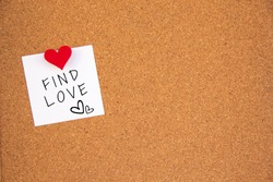 find love letter on white paper fastened to the left with red heart pushpin on cork board