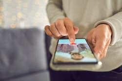 Find love online concept. Adult woman pressing red heart like button below handsome man's profile photo on dating app. Close-up of female hands holding mobile phone. Soft focus, selective focus, blur