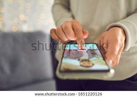 Find love online concept. Adult woman pressing red heart like button below handsome man's profile photo on dating app. Close-up of female hands holding mobile phone. Soft focus, selective focus, blur Stock photo ©
