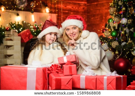 Find presents online. small child girl with mom in santa hat. xmas gift boxes. Open present. merry christmas. mother and daughter love holidays. Winter shopping sales. Happy family celebrate new year.