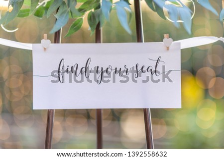 Find your seat sign for wedding or event white card with ribbon and wooden pegs and green leaf foliage above with blurred bokeh background and copyspace for names