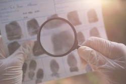 Finding evidence of the investigation of the crime.Hand with Magnifying glass search evidence from police fingerprint crime page file.
