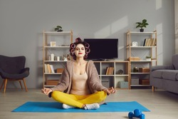 Finding moment of peace and time for self care in hectic domestic lifestyle. Happy calm relaxed woman in beauty face mask and curlers sitting in Lotus pose on yoga mat and meditating with eyes closed