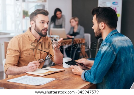 Finding solution together. Two confident young men talking and gesturing while sitting at the desk in office with two colleagues working in the background