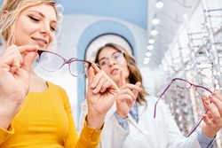 Finding the right frame for prescription glasses, optician suggesting and showing eyeglasses in a optical shop