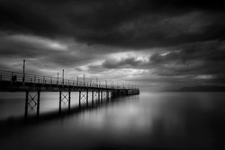 Fine art, black and white long exposure photograph of the old pier in Agia Marina, Stylida, Greece