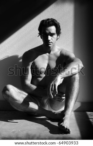 Fine art black and white sensual photo of a young man in underwear