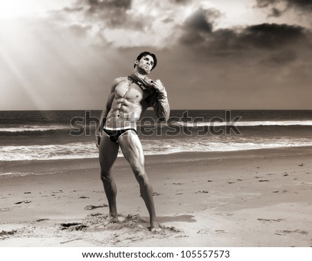 Fine art body portrait of a beautiful muscular man on the beach with dramatic sky and sepia toning