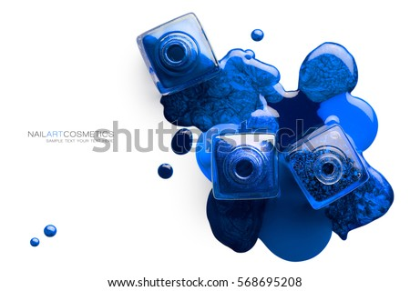 Fine art cosmetics and beauty image of vivid blue nail varnish spilled around three opened bottles viewed top down with different shades and metallic lustre isolated on white with copy space for text