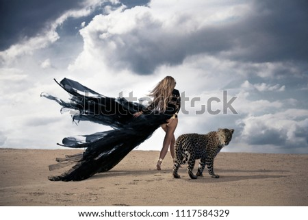 Fine art fashion photo of a mysterious woman with long black dress walking with leopard through the desert