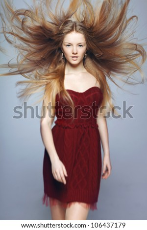 Fine art fashion portrait of blond fashion model posing with hair fluttering in the wind, shallow deep of field