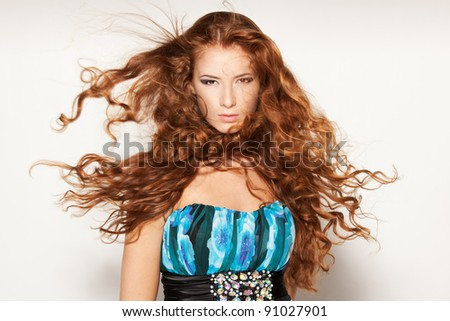 Fine art fashion portrait of red-haired fashion model posing with hair fluttering in the wind