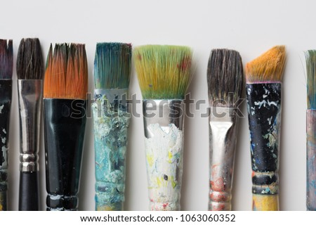 fine art, painting, creativity and artistic tools concept - close up of dirty paintbrushes from top