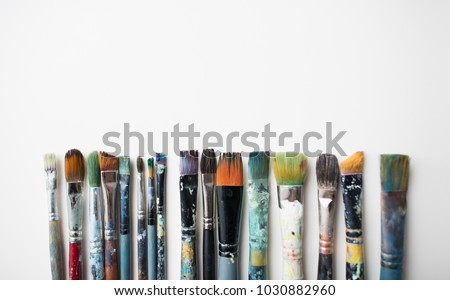 fine art, painting, creativity and artistic tools concept - dirty paintbrushes from top