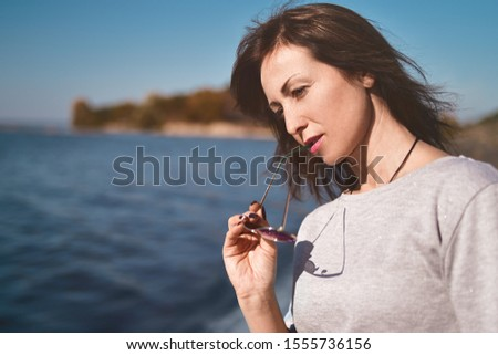 Fine art portrait of a beautiful adult woman on the sea river on the pier. woman thought about something important