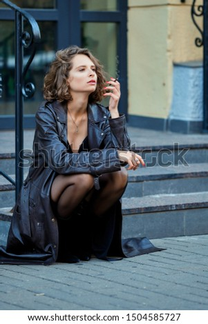 Fine art portrait of a beautiful lady with cigarette sitting on the porch