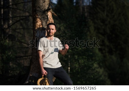 fine art portrait of a hipster man wearing sunglasses in a forest.