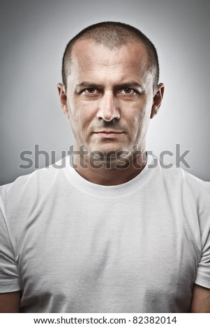 Fine art portrait of a menacing man, studio close up - stock photo