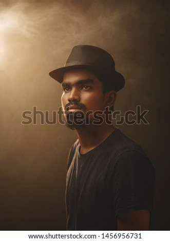 Fine art portrait of bearded young man with hat