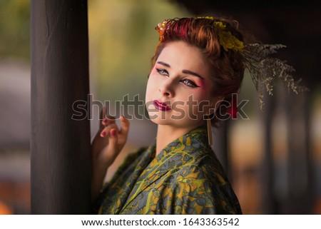 Fine art portrait of beautiful woman in Japanese Geisha style wearing kimono