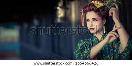 Fine art portrait of beautiful woman in Japanese Geisha style wearing kimono. Panorama