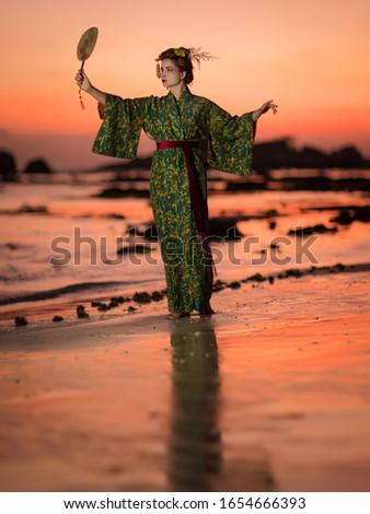 Fine art portrait of european woman in Japanese Geisha style wearing kimono