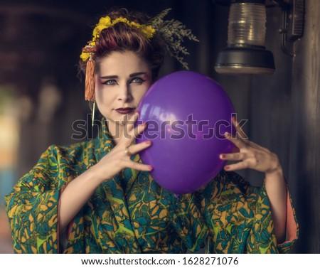 Fine art portrait of european woman in Japanese Geisha style wearing kimono with balloon