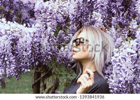 Fine art portrait of girl in dress in lilac garden, Outdoor fashion photo of beautiful young woman surrounded by flowers