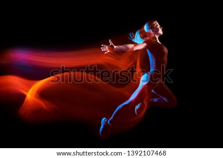 Fine art portrait of young sport woman running, with a light train behind her. Mixed lighting photography.