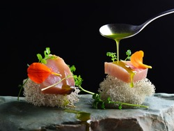 Fine dining, fresh raw ahi tuna sashimi served on sponge with herbs
