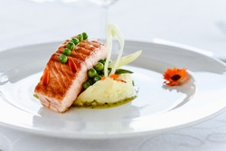 Fine dining salmon steak with peas and mashed potatoes in a white plate with white background
