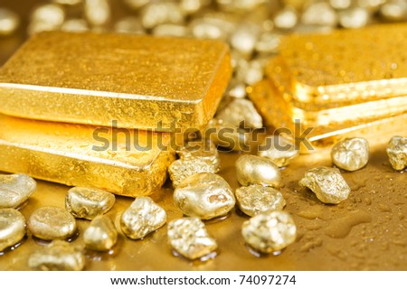 fine gold ingots and nuggets on a wet golden background