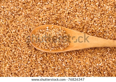Fine-ground barley with spoon as texture