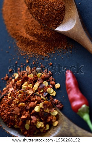 Fine grounded and chopped red chili pepper in two wooden spoons on dark surface, top view.