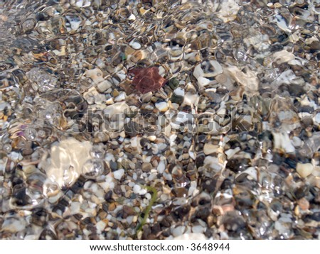 Fine pebble on shoal sea bottom through wave water layer - stock photo