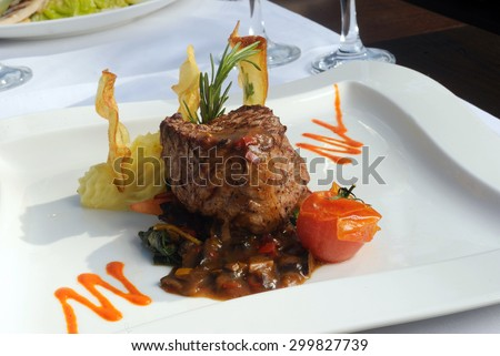 Fine restaurant dinner table place setting: napkin, wineglass, plate, beef and wine