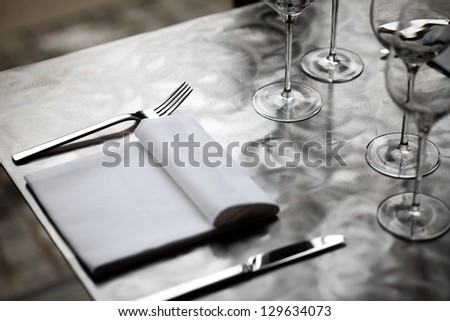 Fine restaurant dinner table place setting with napkin and wineglass