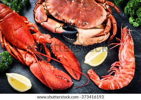 Fine selection of crustacean for dinner. Lobster, crab and jumbo shrimp on dark background