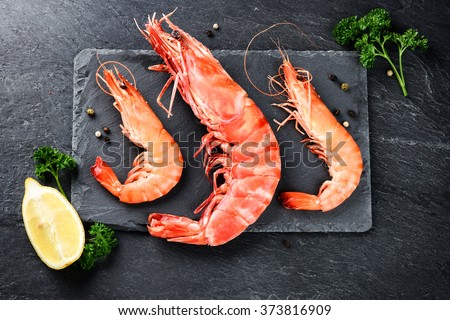 Shutterstock Fine selection of jumbo shrimps for dinner on stone plate. Food background