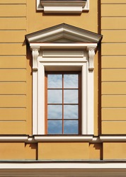 Fine window decorated with portico and pilasters