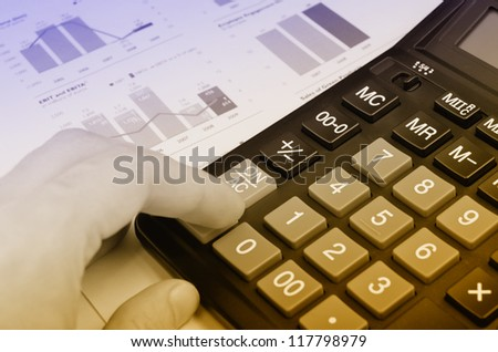 Finger and calculator over annual report