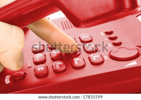 finger and keypad. dialing on red telephone