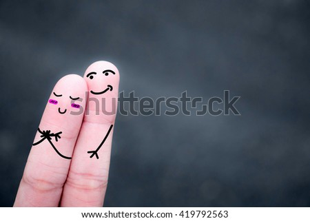 Finger art of a Happy couple. A man and a woman hug with pink hearts in the eyes. The concept of love at first sight.. #419792563