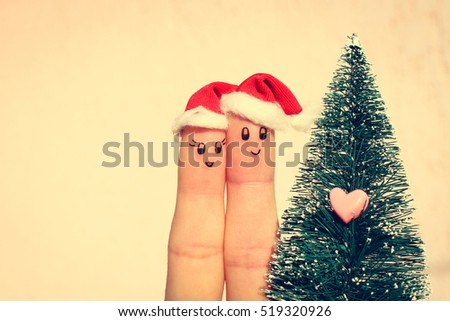 Finger art of couple celebrates Christmas. Concept of man and woman laughing in new year hats near Christmas tree. Toned image.