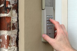 finger entering code on Keypad used on a garage door entrance to a home - security keypad - security code