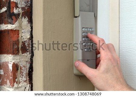 finger entering code on Keypad used on a garage door entrance to a home - security keypad - security code #1308748069