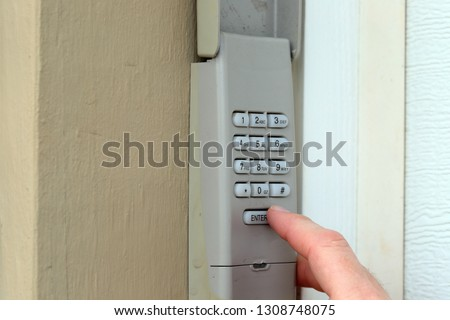 finger entering secret code on a keypad used on a garage door entrance to a home - security keypad - security code #1308748075
