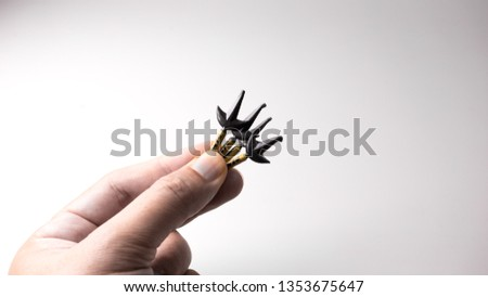 "Finger holding mini Japanese traditional ninja warrior weapon called kunai with kanji writing of ""shinobu"", meaning to endure or conceal. Concept of endurance. Isolated on empty background. Copy space #1353675647"